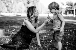 mother and son blowing dandelions at city park kelowna